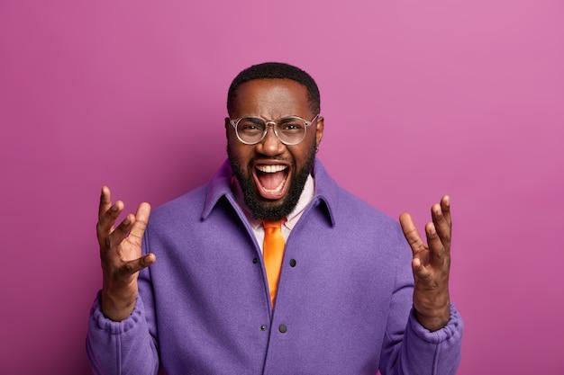 Portret van geïrriteerde zwarte man houdt handen omhoog, mond open, schreeuwt van irritatie, is het ergens niet mee eens, gekleed in paars jasje