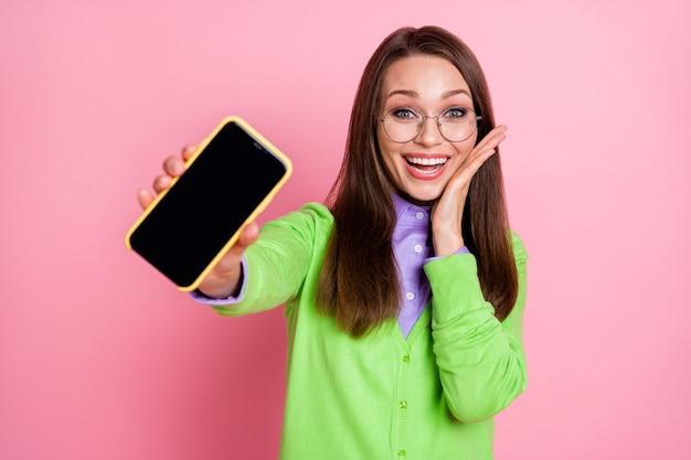 Portret van gek verbaasd meisje houdt smartphone geïsoleerd over pastelkleurige achtergrond
