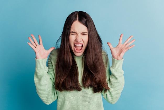 Portret van gekke agressieve vrouw schreeuw geïsoleerd op groenblauw achtergrond