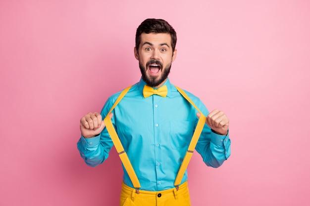 Portret van gekke bebaarde man bretels met plezier trekken