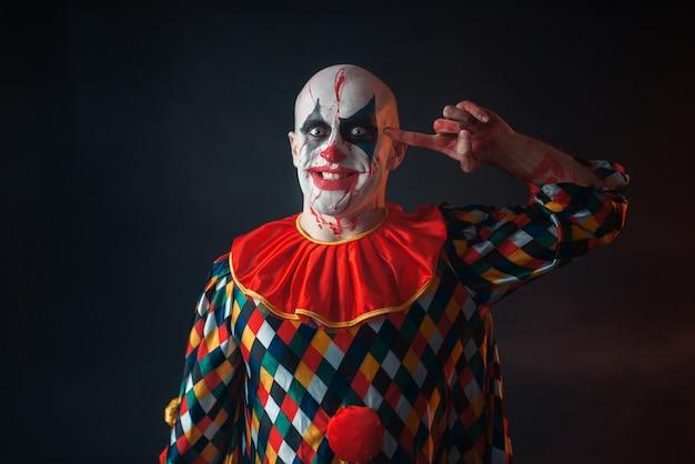 Portret van gekke bloedige clown dwarrelt vinger naar zijn tempel