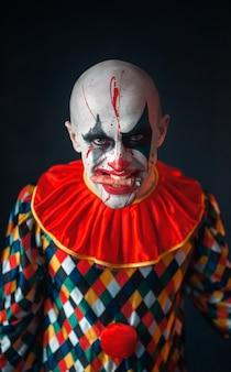 Portret van gekke bloedige clown, gezicht in bloed