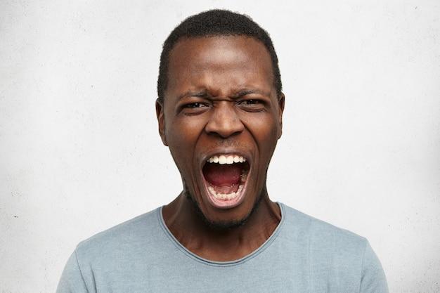 Portret van gekke boze jonge donkere man terloops gekleed, schreeuwend van woede
