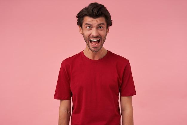 Portret van gekke boze jonge man met varkenshaar en geopende mond in rode t-shirt ziet er boos en schreeuwend uit