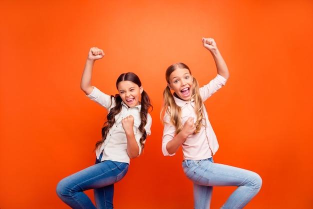 Portret van gekke extatische sportfan kinderen kijken teamspel vieren overwinning schreeuwen ja, vuisten heffen draag moderne casual stijl kleding geïsoleerd op felle kleur achtergrond
