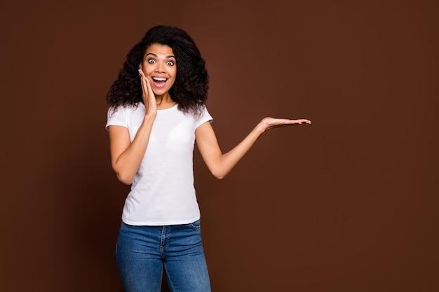 Portret van gekke funky afro-amerikaanse meid houdt hand aanwezig prachtige zwarte vrijdag optie schreeuw kiezen beslissen adviseren advertentie promotie slijtage denim jeans.