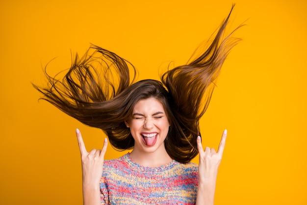 Portret van gekke funky opgewonden meisje rock fan maken gehoornde symbool toon tong uit sluiten ogen genieten verheug je haar kapsel vliegen dragen pullover geïsoleerd over heldere glans gele kleur