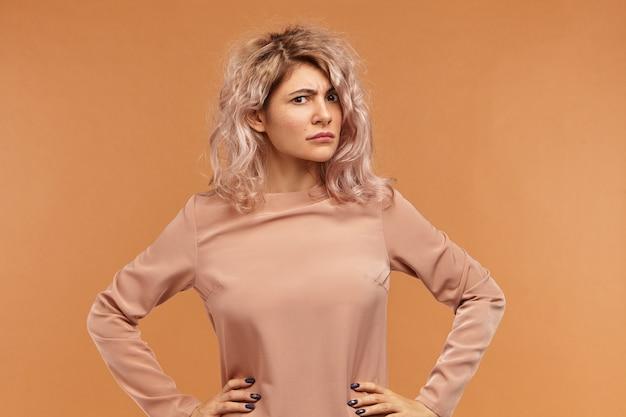 Portret van gekke jonge vrouw met omvangrijke kapsel handen houden op haar taille,
