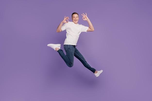 Portret van gekke promotor man sprong run handen tonen oke op paarse achtergrond