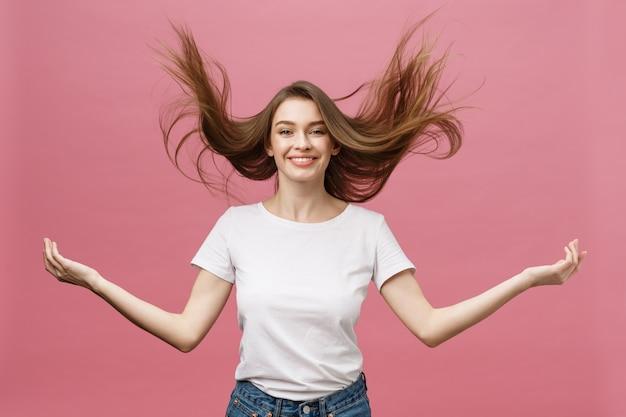 Portret van gekke schattige jonge vrouw speelt met haar haren