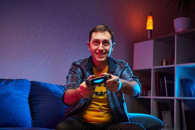 Portret van gekke speelse gamer, jongen genieten van spelen van videogames binnenshuis zittend op de bank, console gamepad in handen te houden. thuis rusten, een fijn weekend gewenst
