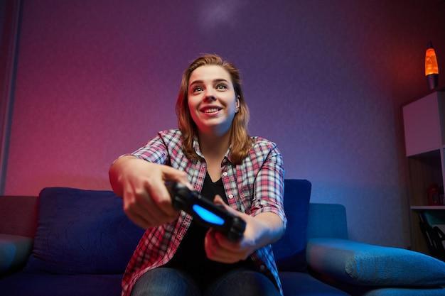 Portret van gekke speelse gamer, meisje genieten van het spelen van videogames binnenshuis zittend op de bank, console gamepad in handen te houden. thuis rusten, een fijn weekend gewenst