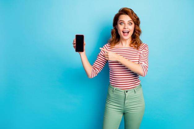 Portret van gekke verbaasde meid houdt nieuwe moderne smartphone punt wijsvinger adviseren kies schreeuw wow omg draag witte trui geïsoleerd over blauwe kleur