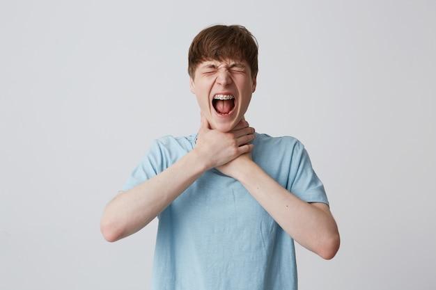 Portret van gekke wanhopige jongeman student met gesloten ogen en accolades op tanden draagt blauw t-shirt