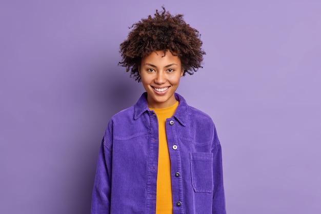 Portret van gekrulde haired mooie vrouw glimlacht gelukkig draagt modieuze paarse jas in één toon met achtergrond voelt opgetogen poses blij indoor gesprekken met collega. positieve emoties concept