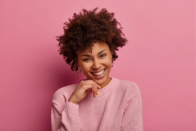 Portret van gekrulde vrouw raakt kin, kantelt hoofd, grijnst en staart, gekleed in trui, drukt positiviteit en vreugde uit, draagt casual trui, geïsoleerd over roze pastel muur