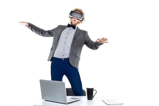Portret van gekrulde zakenman die vr-bril gebruikt terwijl hij op stoel aan tafel staat met gadgets en kopje koffie.