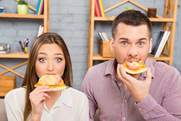 Portret van geliefden die pizza eten
