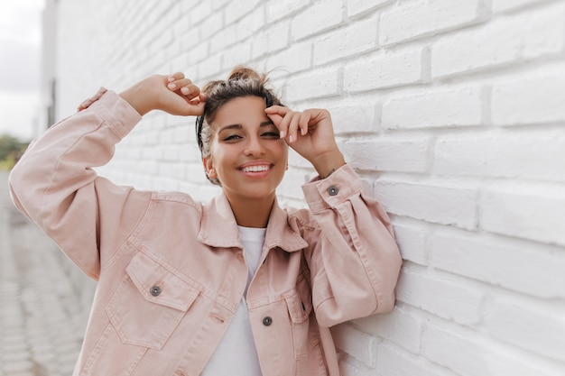 Portret van gelooide jonge brunette vrouw in lichte denim jasje poseren tegen wit gebouw
