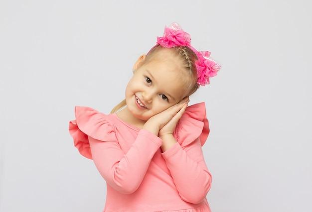 Portret van gelukkig 5 jaar oud meisje dat op grijze achtergrond wordt geïsoleerd
