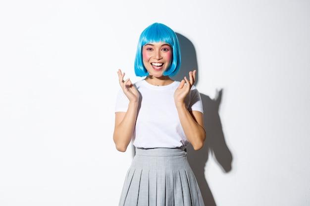 Portret van gelukkig aantrekkelijk aziatisch meisje in de handen van de blauwe overhemdspruik klappen, applaus en glimlachen bij camera.