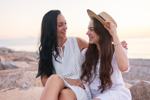 Portret van gelukkig aantrekkelijke glimlachende dochter en moeder in witte jurken knuffelen en kijken elkaar in de zomer bij zonsondergang aan zee