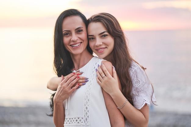 Portret van gelukkig aantrekkelijke glimlachende dochter en moeder knuffelen in de zomer bij zonsondergang aan zee