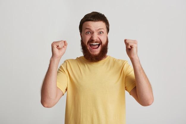 Portret van gelukkig aantrekkelijke jonge man hipster met baard draagt t-shirt ziet er zelfverzekerd en opgewonden uit