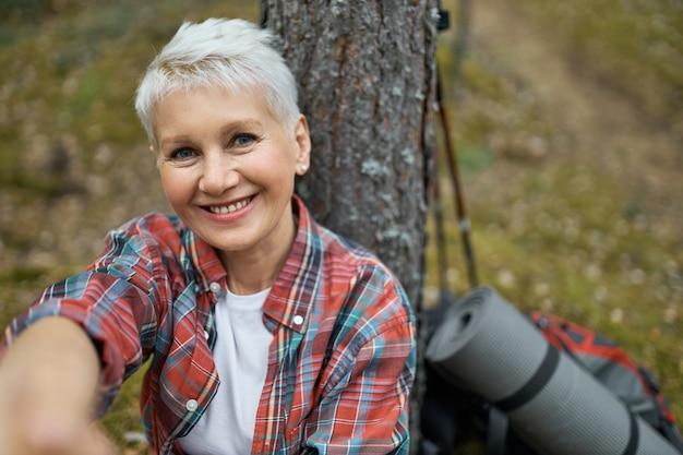 Portret van gelukkig aantrekkelijke vrouw van middelbare leeftijd met blond haar, zittend onder dennen camera kijken met glimlach, hand reiken alsof het nemen van selfie op slimme telefoon, pauze, buiten wandelen