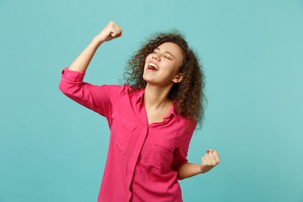 Portret van gelukkig afrikaans meisje in roze casual kleding balde vuisten als winnaar geïsoleerd op blauwe turquoise muur achtergrond in studio. mensen oprechte emoties, lifestyle concept. bespotten kopie ruimte.