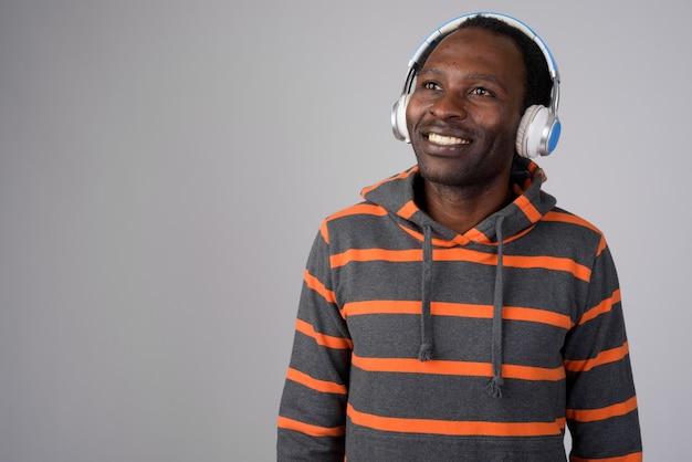 Portret van gelukkig afrikaanse man denken tijdens het luisteren naar muziek