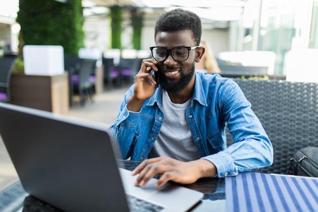 Portret van gelukkig afrikaanse zakenman met behulp van telefoon tijdens het werken op laptop in een restaurant