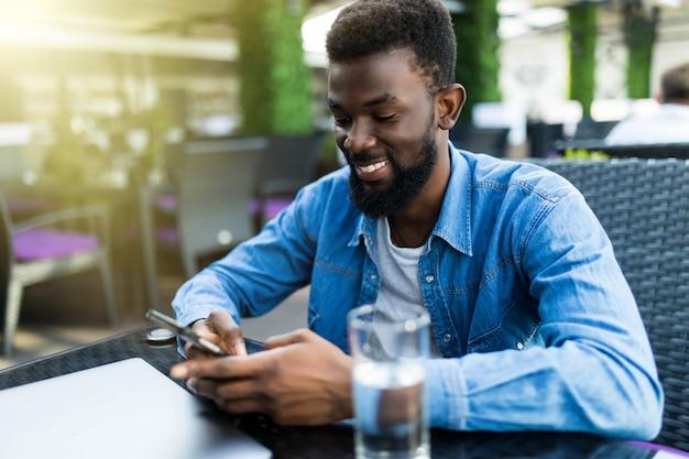 Portret van gelukkig afro-amerikaanse man zit in café met mobiele telefoon close-up