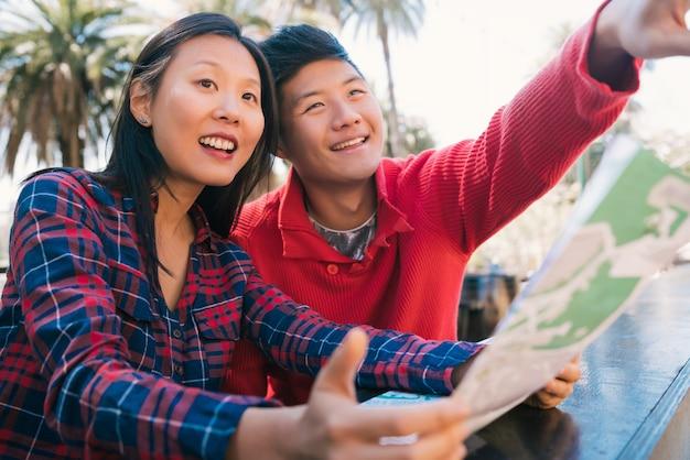 Portret van gelukkig aziatisch reizigerspaar dat een kaart houdt en richtingen zoekt. reis- en vakantieconcept.