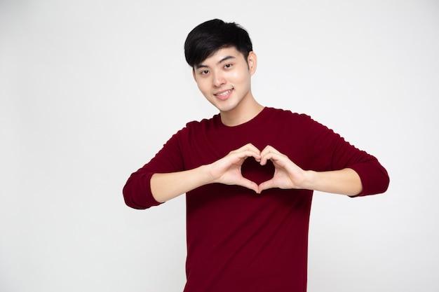 Portret van gelukkig aziatische man die hart met vingers geïsoleerd op een witte achtergrond