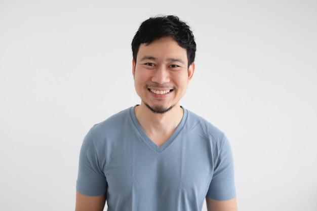 Portret van gelukkig aziatische man in blauw t-shirt op geïsoleerde witte muur.