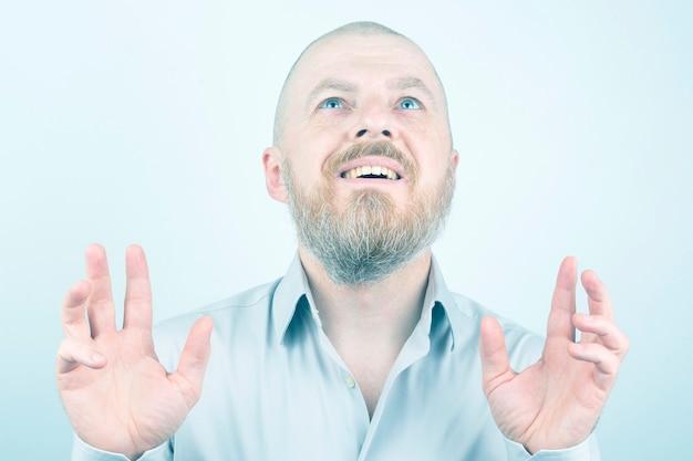 Portret van gelukkig bebaarde man met opgeheven handen op lichte achtergrond. zijn innerlijke wereld