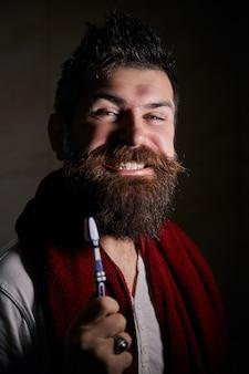 Portret van gelukkig bebaarde man met tandenborstel tanden poetsen, de tanden poetsen in de ochtend.