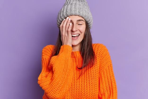 Portret van gelukkig brunette vrouw bedekt gezicht met hand giechelt positief ogen sluit positieve emoties draagt gebreide muts en trui.
