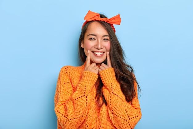 Portret van gelukkig donkerharig koreaans meisje met brede glimlach, houdt wijsvingers dichtbij mond, draagt oranje hoofdband en gebreide trui