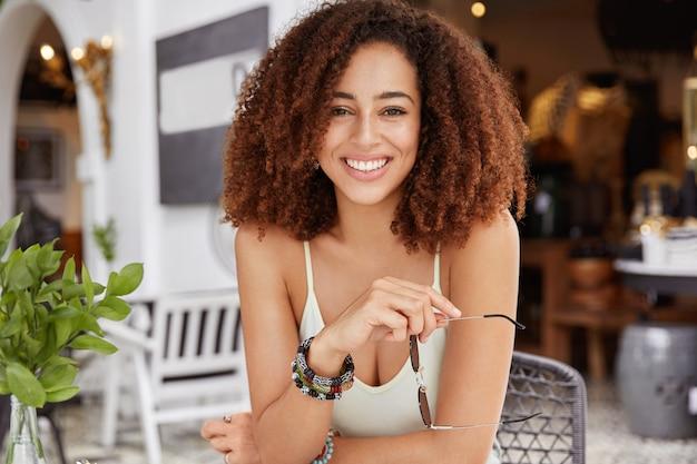 Portret van gelukkig donkerhuidige krullende afrikaanse jonge vrouw met opgetogen uitdrukking, zonnebril houdt, zomervakantie doorbrengt in tropisch land