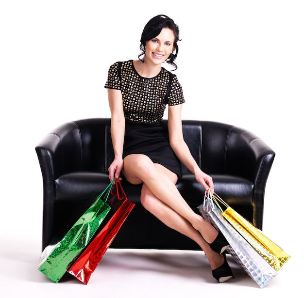 Portret van gelukkig elegante vrouw in zwarte jurk met boodschappentassen zittend op de bank geïsoleerd op een witte achtergrond.