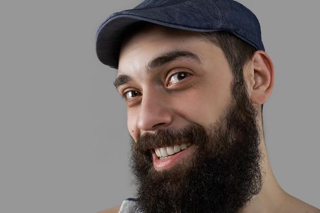 Portret van gelukkig en lachende bebaarde man in studio op grijze achtergrond close-up.
