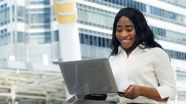 Portret van gelukkig en verrassend zakelijke afrikaanse vrouw maakt gebruik van computer laptop
