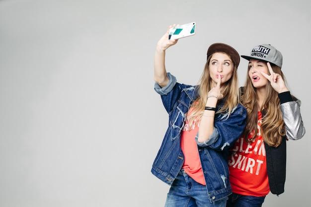 Portret van gelukkig gelukkig vrouw in trendy stijl met lang haar. geef jezelf aan de smartphone. het meisje in het spijkerjack raakt haar vinger aan met haar vinger, haar vriendin poseert.