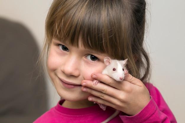 Portret van gelukkig glimlachend leuk kindmeisje met witte huisdierenhamster