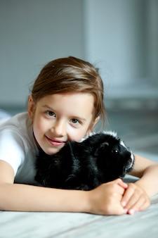 Portret van gelukkig glimlachend meisje die zwart proefkonijn koesteren.
