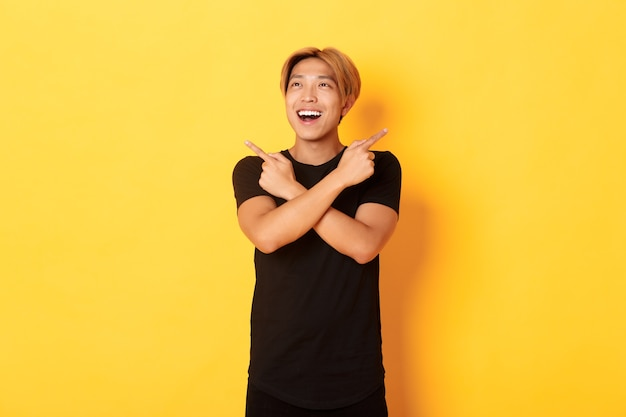 Portret van gelukkig glimlachende aziatische man met blond haar, geamuseerd naar links kijkend, zijwaarts wijzend naar twee varianten, gele muur