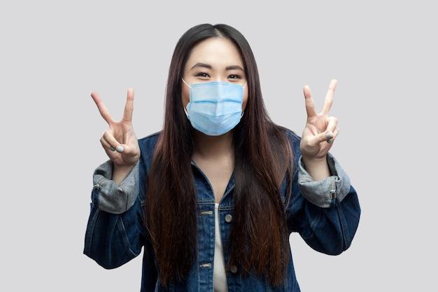Portret van gelukkig grappig mooi brunette aziatisch meisje met medisch masker in blauw spijkerjasje dat staat en naar de camera kijkt met overwinnings- of vredesteken. studio opname, geïsoleerd op een grijze achtergrond.