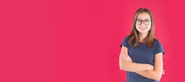 Portret van gelukkig grappig tienermeisje over rode achtergrond.